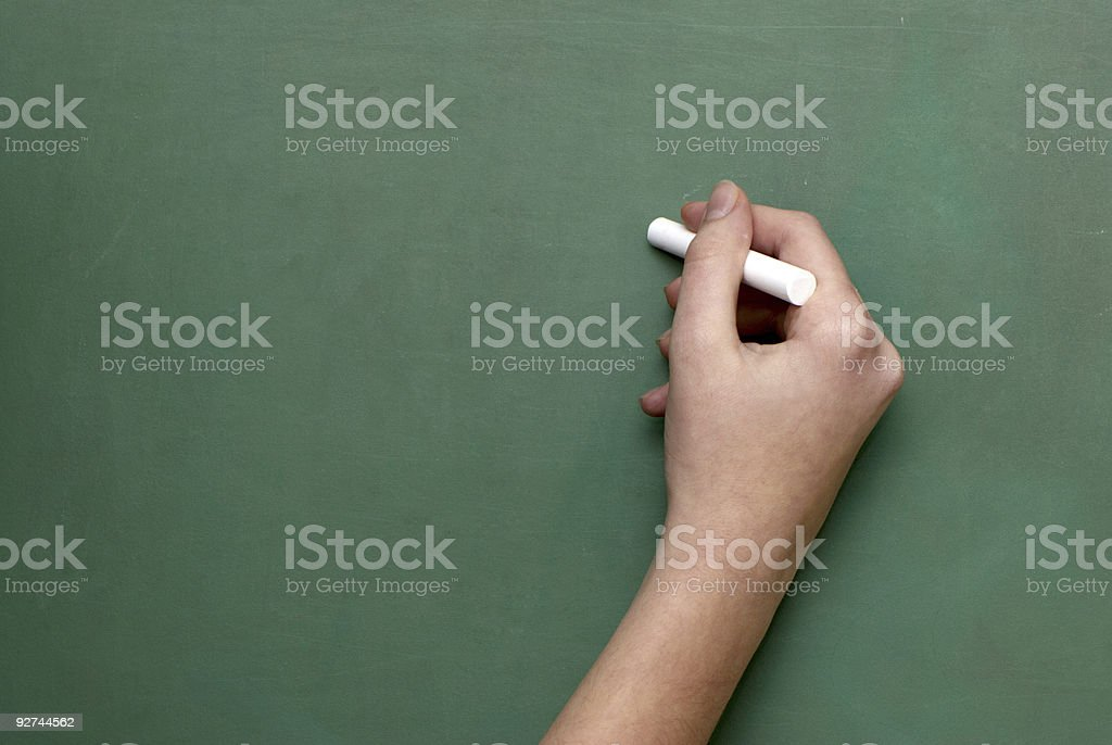 Man holds a piece of chalk royalty-free stock photo