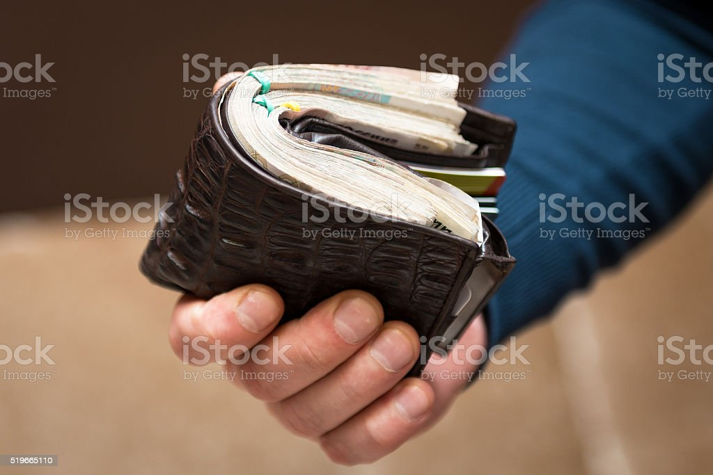 Man holds a purse with money stock photo