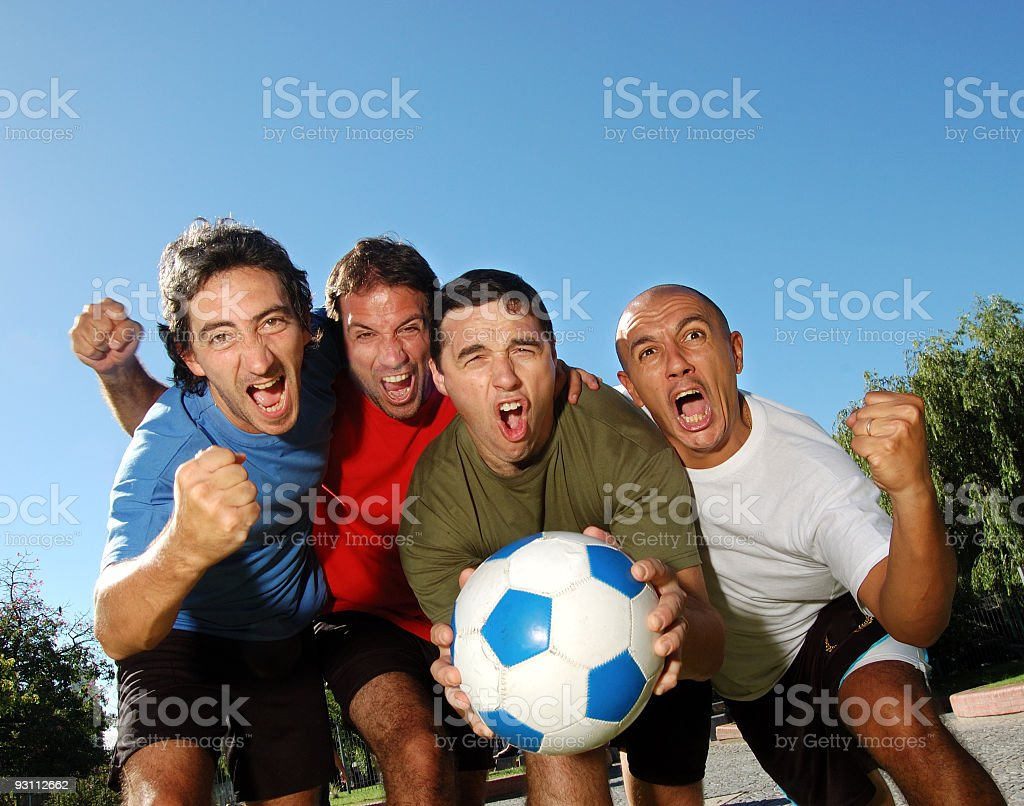 A man holds a soccer ball while 3 others hold up their fists stock photo