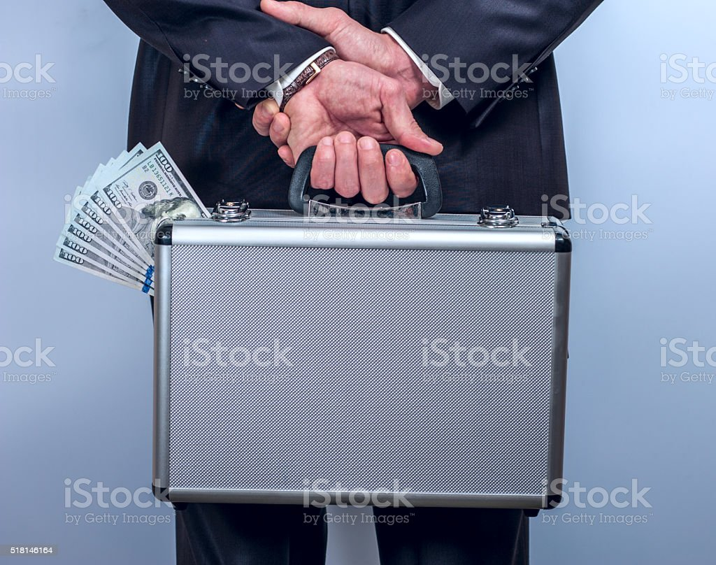 Man holds a suitcase with money behind the back stock photo