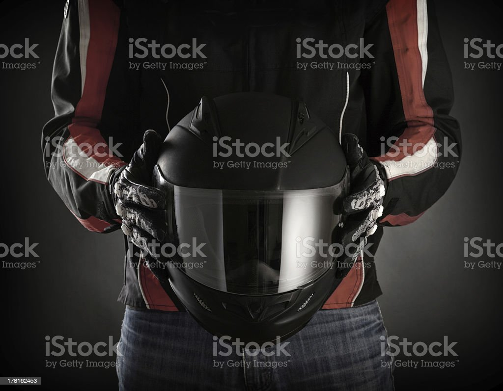 Man holds black motorcycle helmet with visor stock photo
