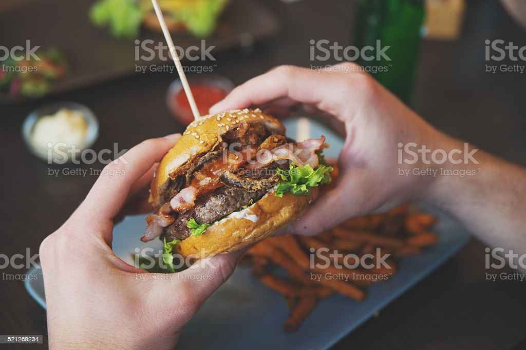man holds burger with hands and sweet potato fries stock photo