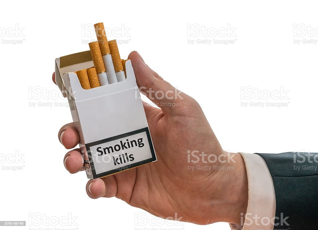 Man holds cigarette pack with warning label that smoking kills. stock photo