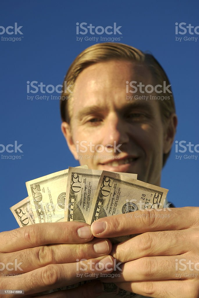 Man Holds Dollar Bills Cash in Blue Sky royalty-free stock photo