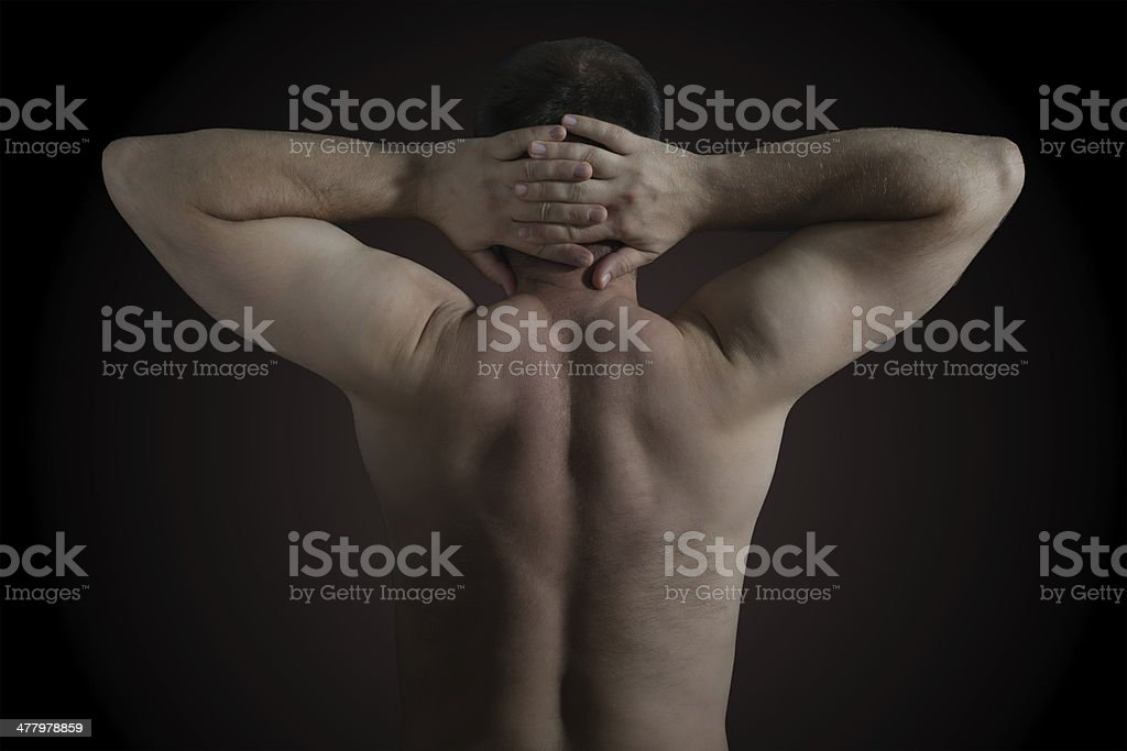Man holds head with his back toward the camera royalty-free stock photo