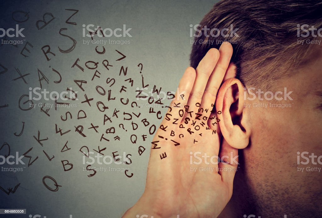 man holds his hand near ear and listens carefully alphabet letters flying stock photo
