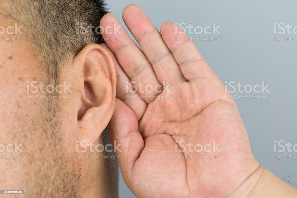 man holds his hand near his ear and listening stock photo