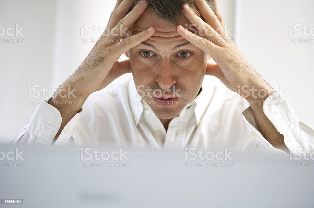 A man holds his head in his hands, looking under stress stock photo