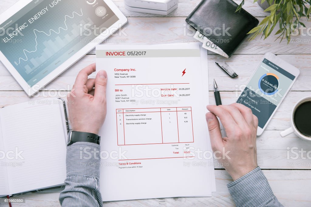 Man holds invoice of electric power usage over desk. stock photo