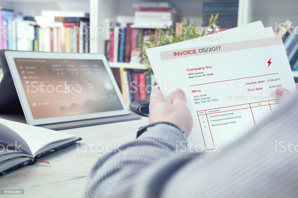 Man holds invoice of electric power usage stock photo