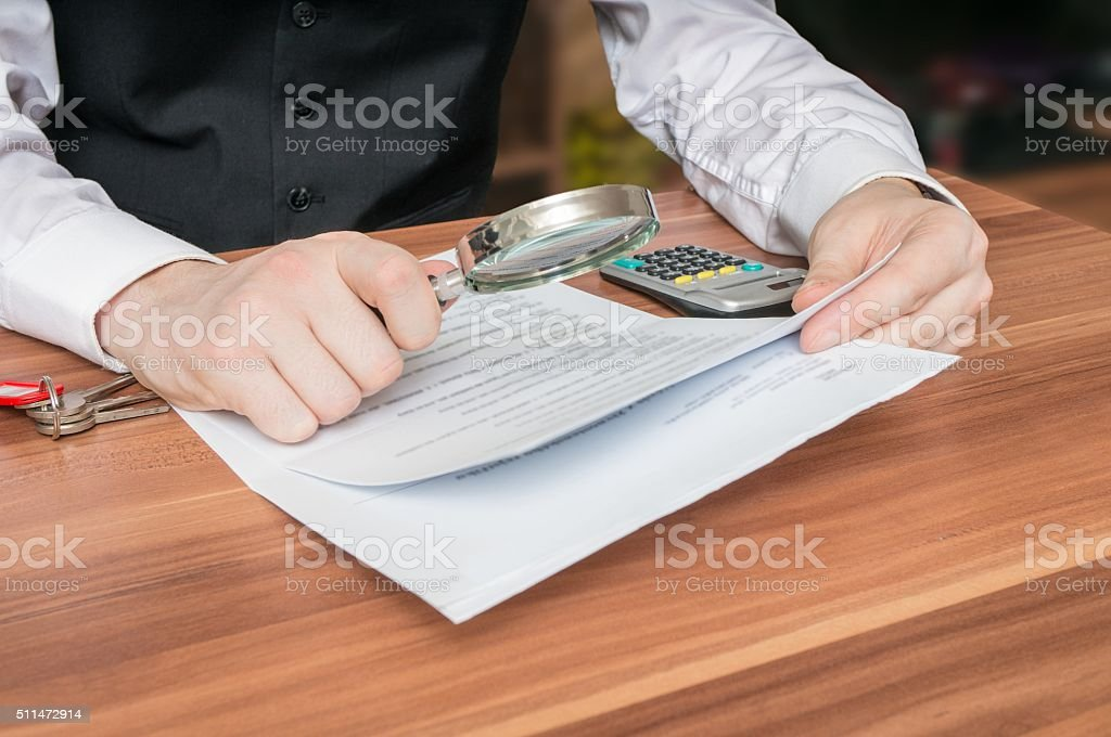 Man holds magnifying glass and is reading contract. stock photo