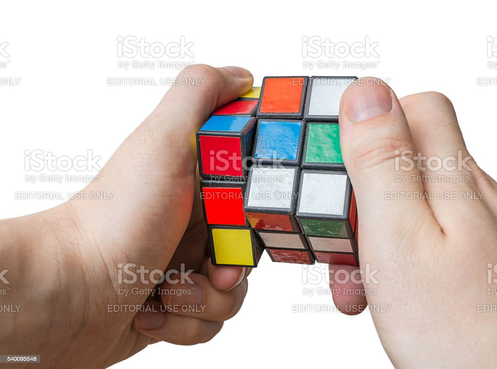 Man holds rubiks cube in hands. stock photo