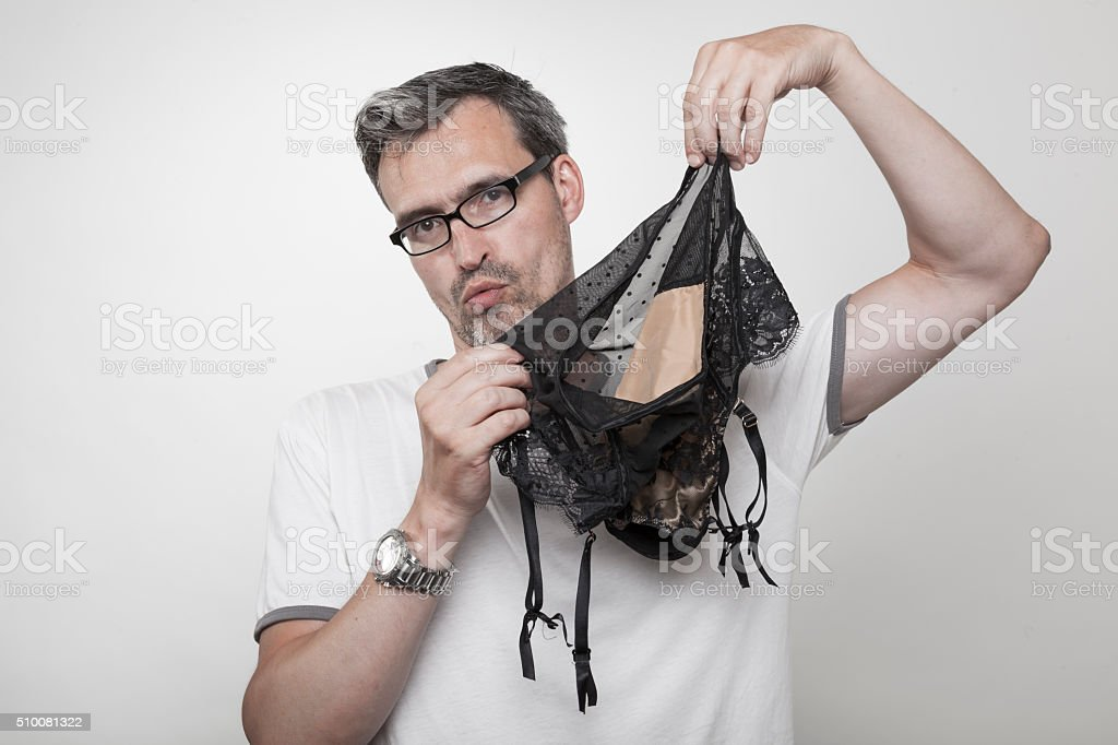 man holds sexy garter belt lingerie in his hands stock photo