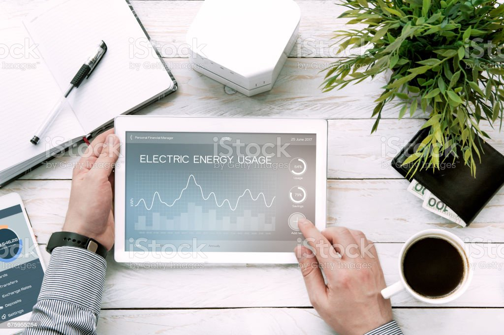 Man holds tablet pc with electric energy usage application. stock photo