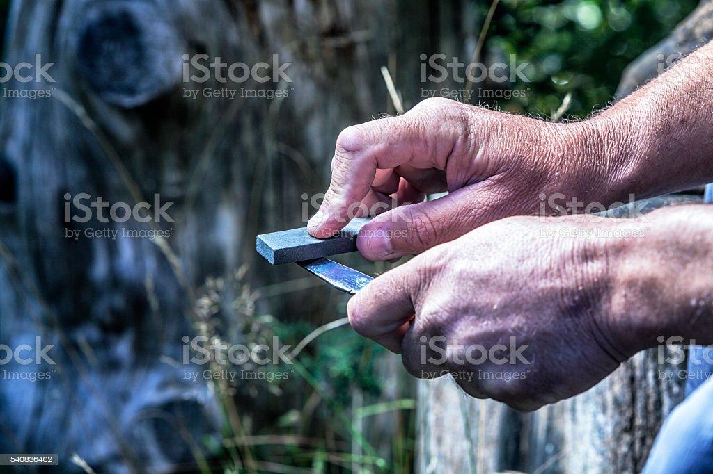 Man Honing Edge of Whittling Knife Blade With Sharpening Stone stock photo