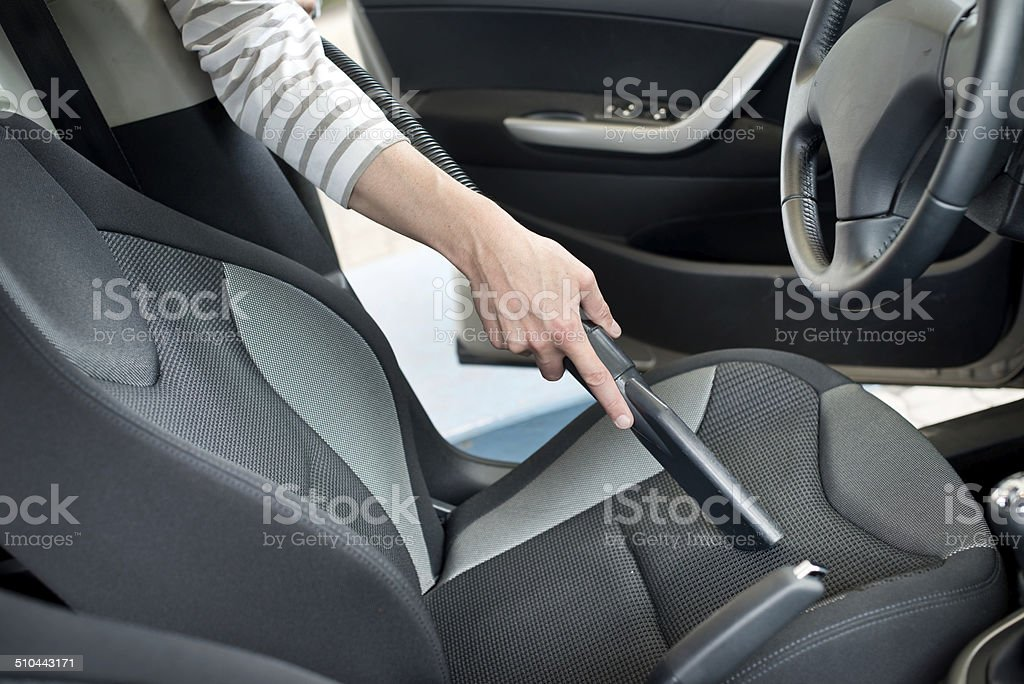 Man hoovering a car cabin stock photo