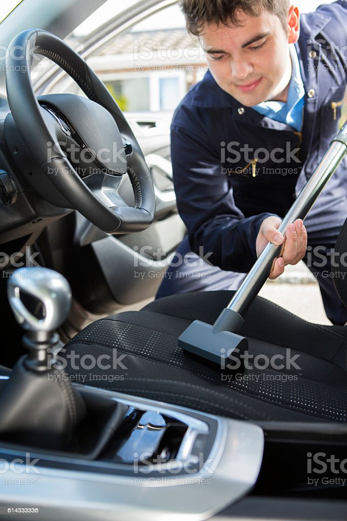Man Hoovering Seat Of Car During Car Cleaning stock photo