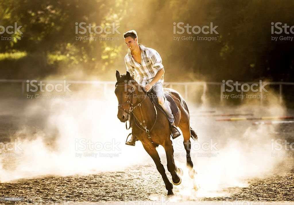 Man horseback riding at sunset. royalty-free stock photo