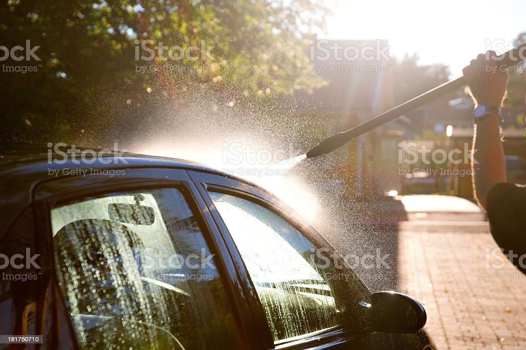Man hosing down a car in the sun stock photo