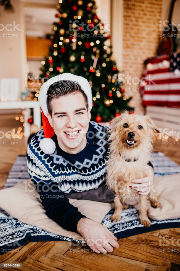 Man hugging his dog in front of a Christmas tree. stock photo