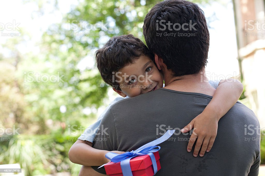 Man hugging smiling young boy holding gift outdoors stock photo