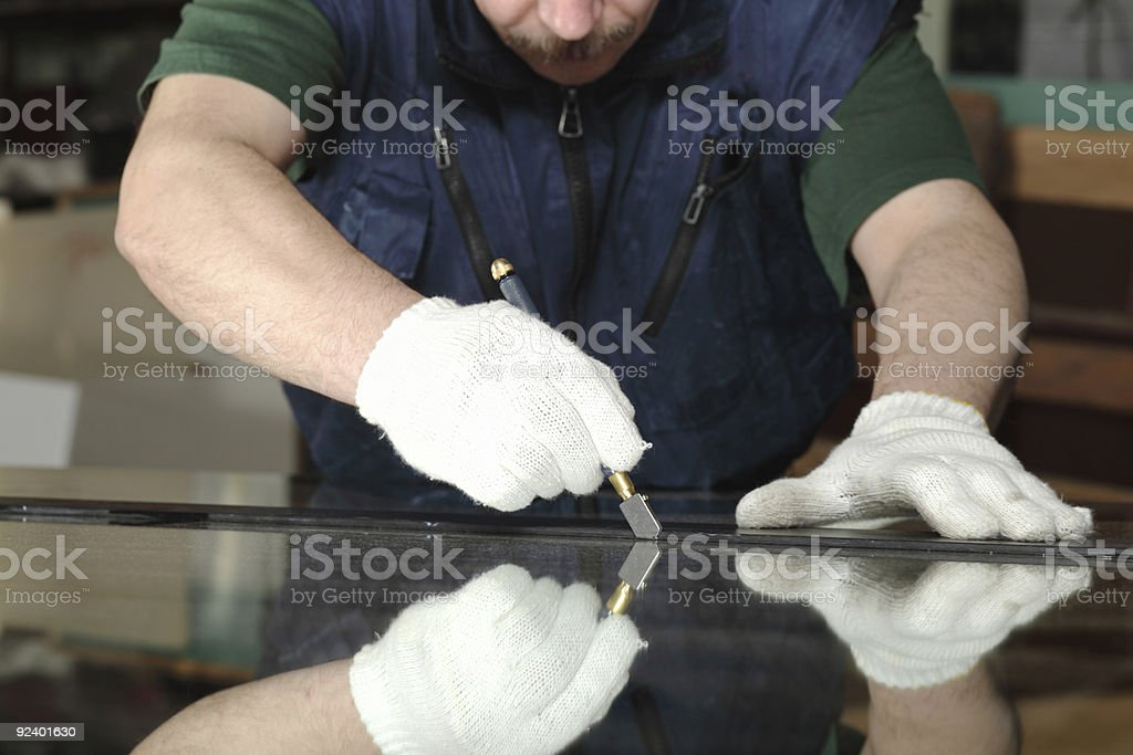Man hunched over a table working stock photo