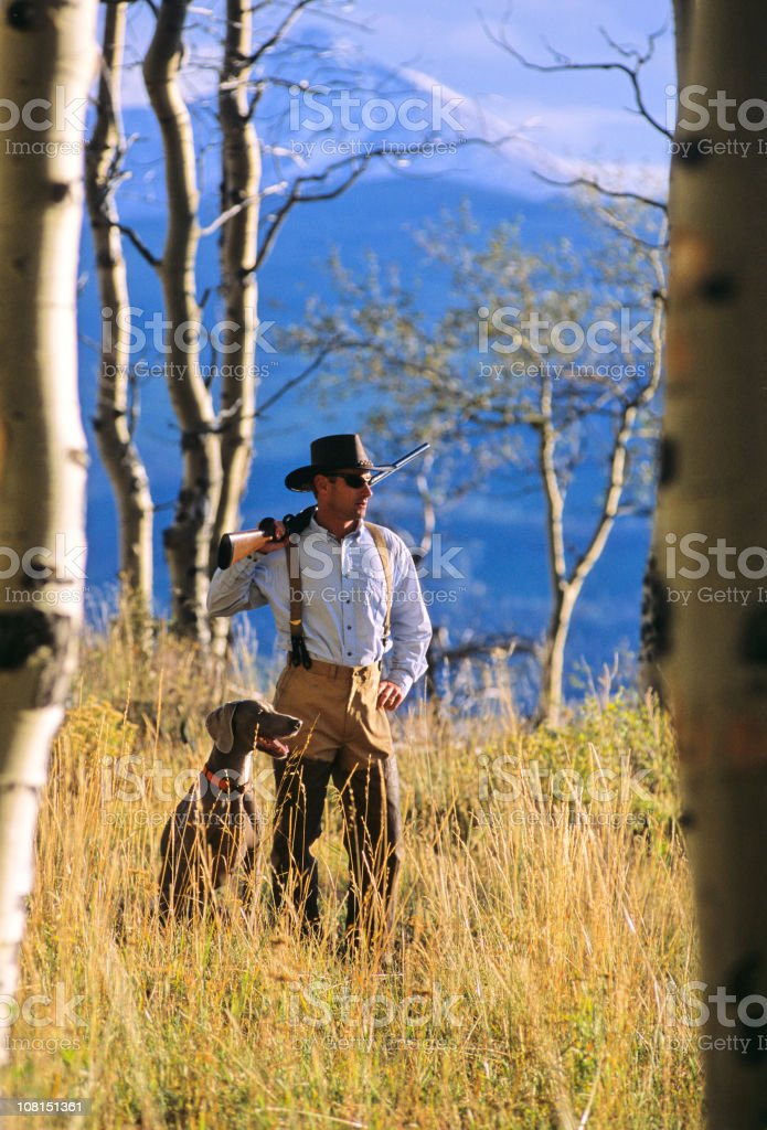 Man Hunting in the Mountains with Dog stock photo