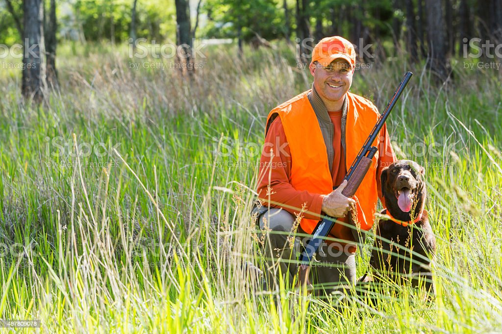 Man hunting with shotgun kneeling next to retriever stock photo