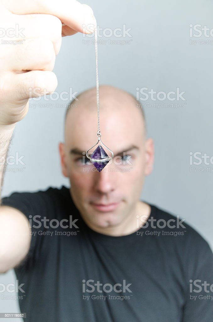 Man hypnotist with crystal pendulum in front of camera stock photo