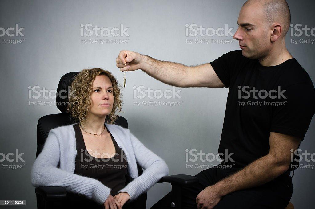 Man hypnotizing pretty woman  with pendulum stock photo