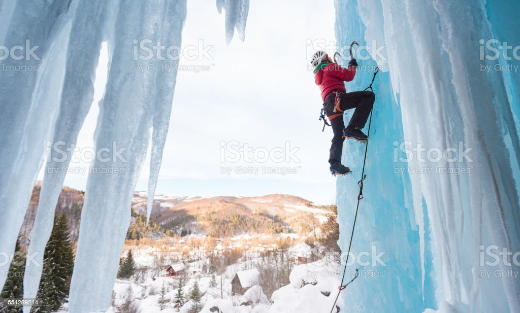 Man ice climbing on frozen waterfall stock photo