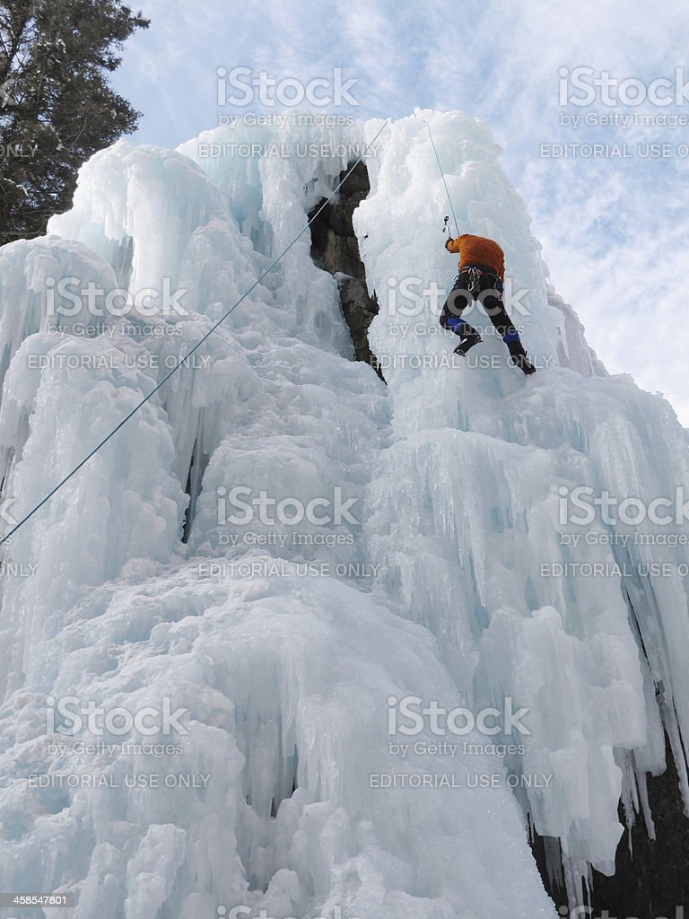 Man ice climbing up a cliff of ice stock photo