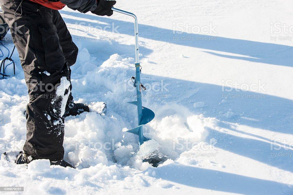 Man Ice Fishing, Great Slave Lake, Yellowknife, Northwest Territories. stock photo
