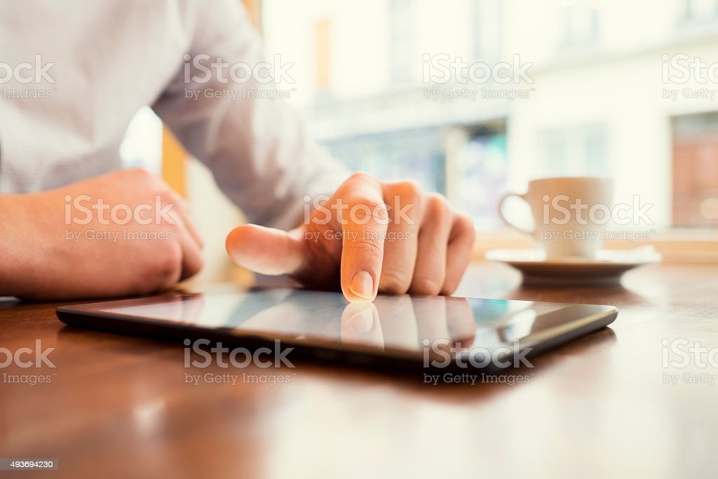Man in a bar using tablet pc. Window background. stock photo