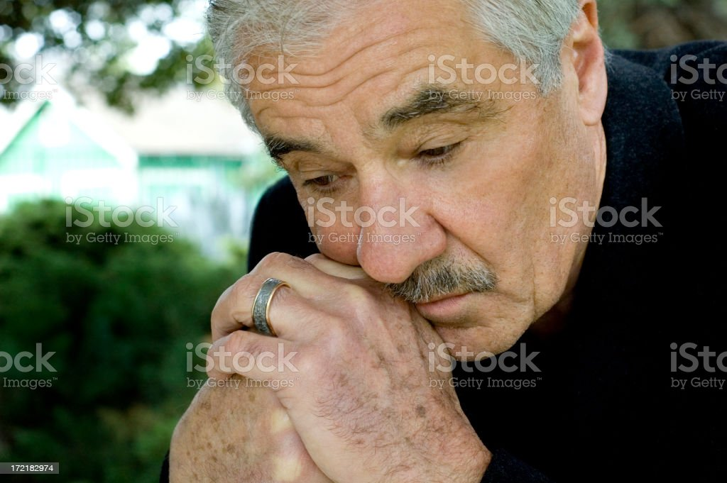 A man in a black shirt is looking solemn and contemplating royalty-free stock photo