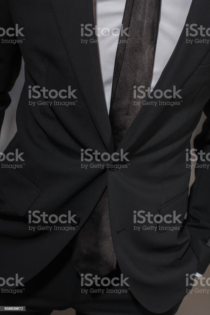 A man in a black suit and a white shirt stock photo