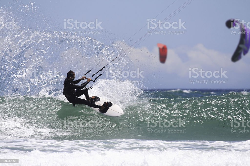 Man in a black wetsuit kitesurfing on the ocean waves stock photo