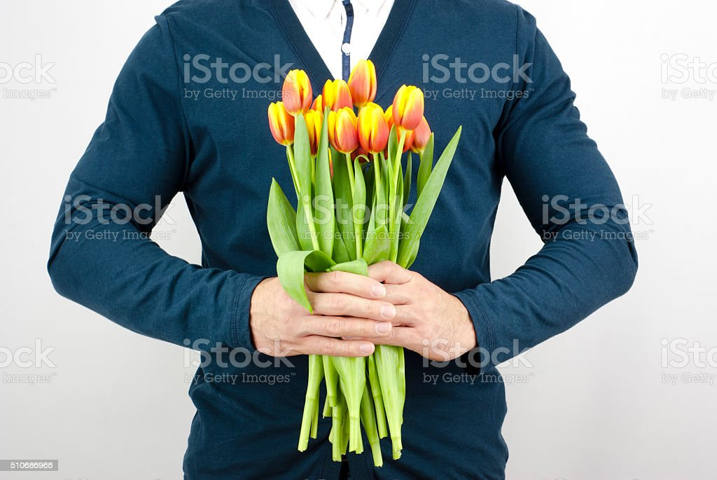 Man in a blue jacket holding a bouquet of tulips stock photo