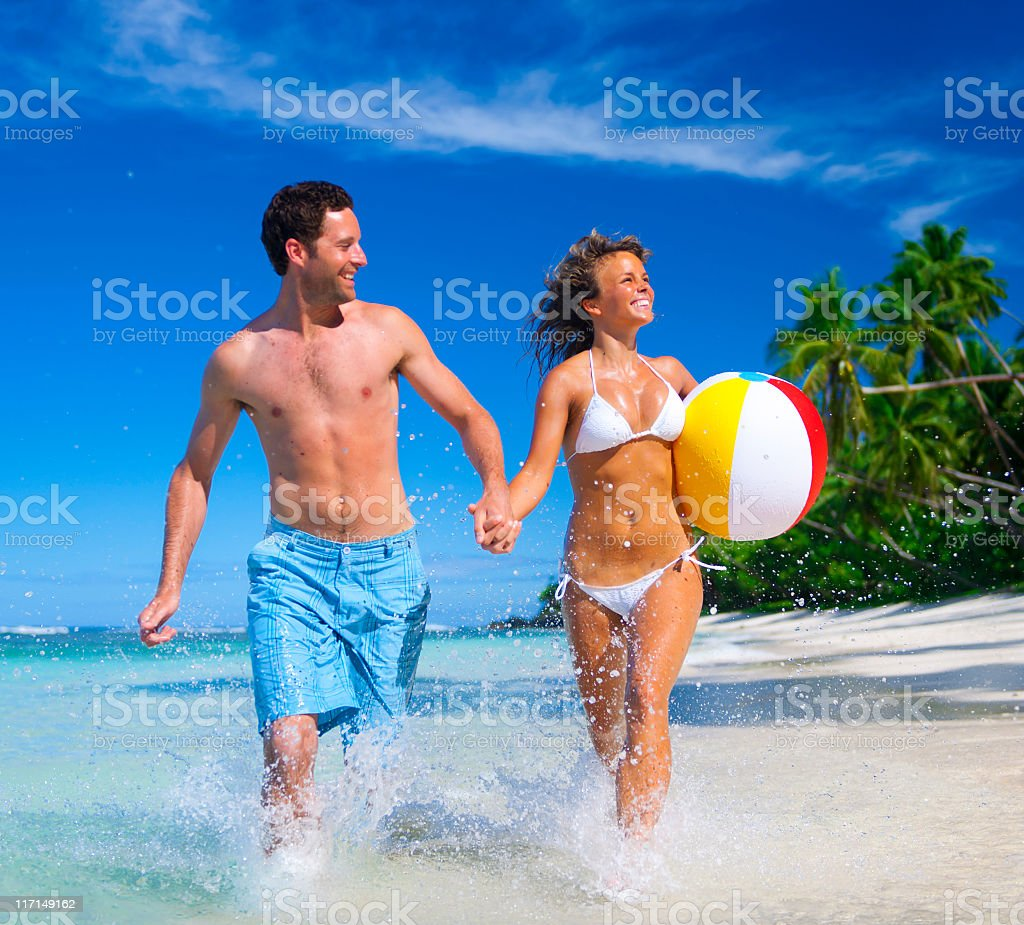 Man in a blue shirt and woman in white swimsuit on the beach royalty-free stock photo