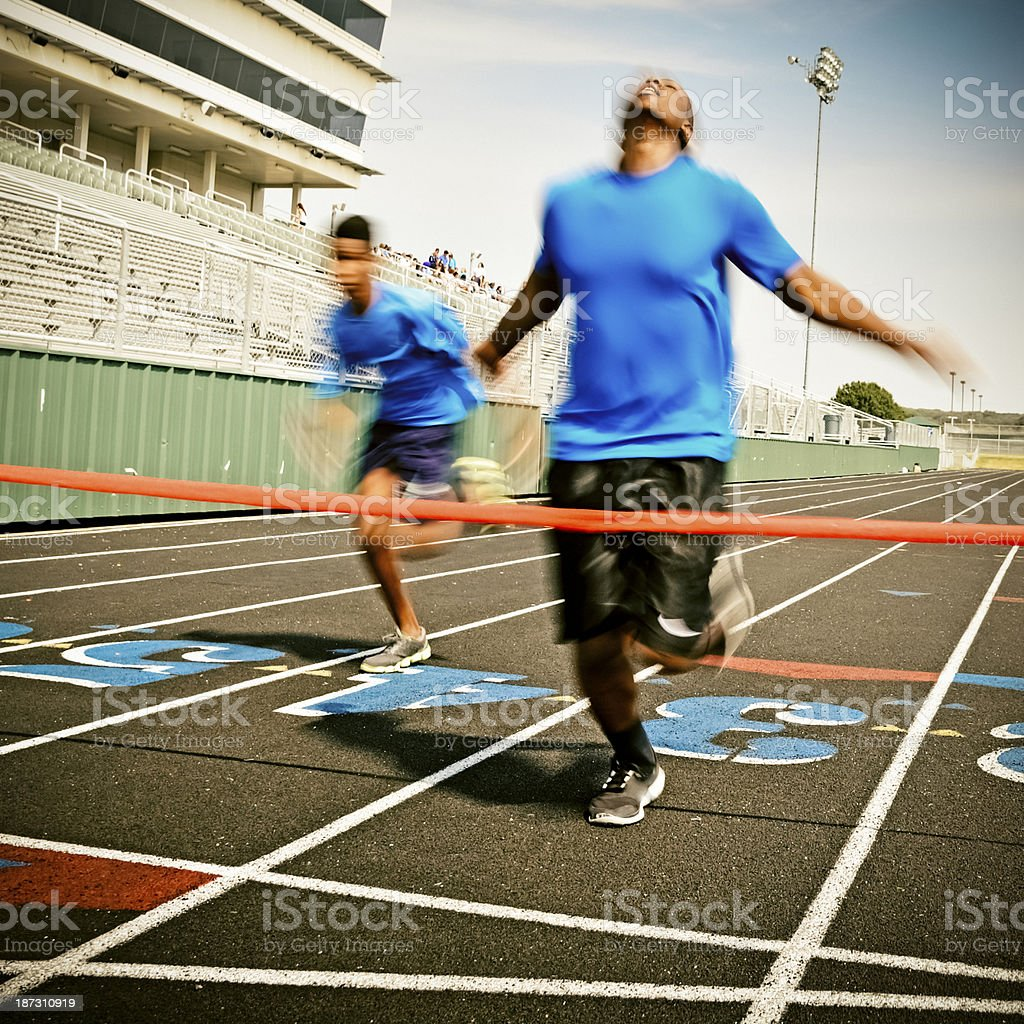 Man in a blue shirt racing towards the finish line stock photo