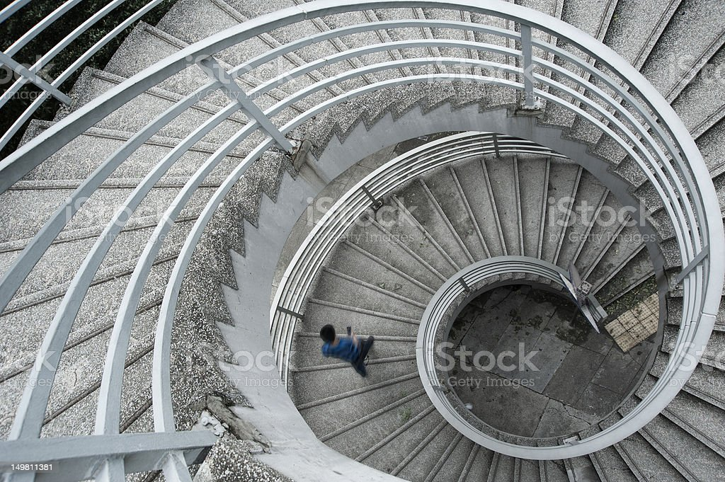 Man in a blue shirt walking down a spiral staircase stock photo