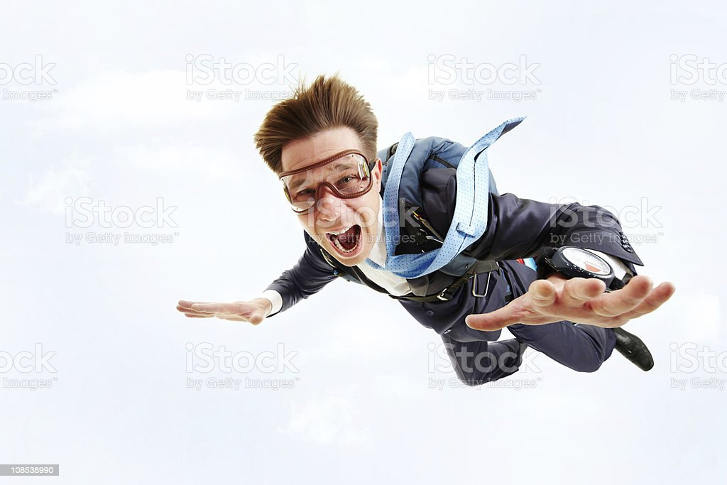 A man in a blue suit and goggles parachuting royalty-free stock photo