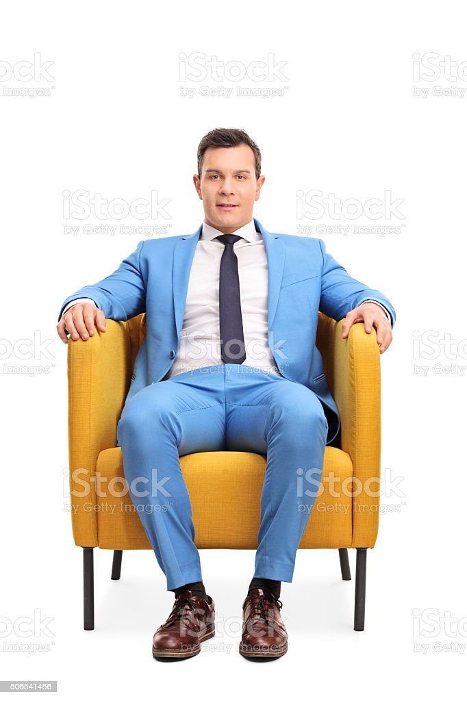 Man in a blue suit sitting in an armchair stock photo
