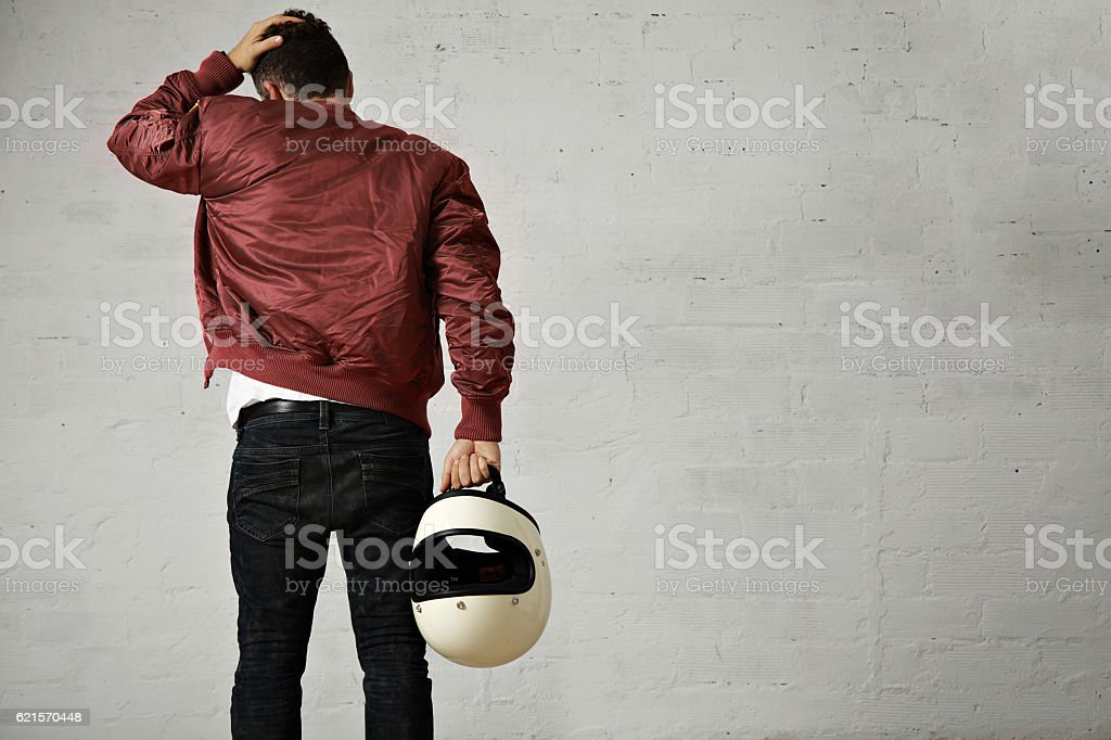 Man in a bordeaux pilot jacket with helmet stock photo