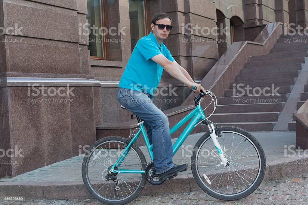 Man in a bright shirt on a bicycle. People stock photo