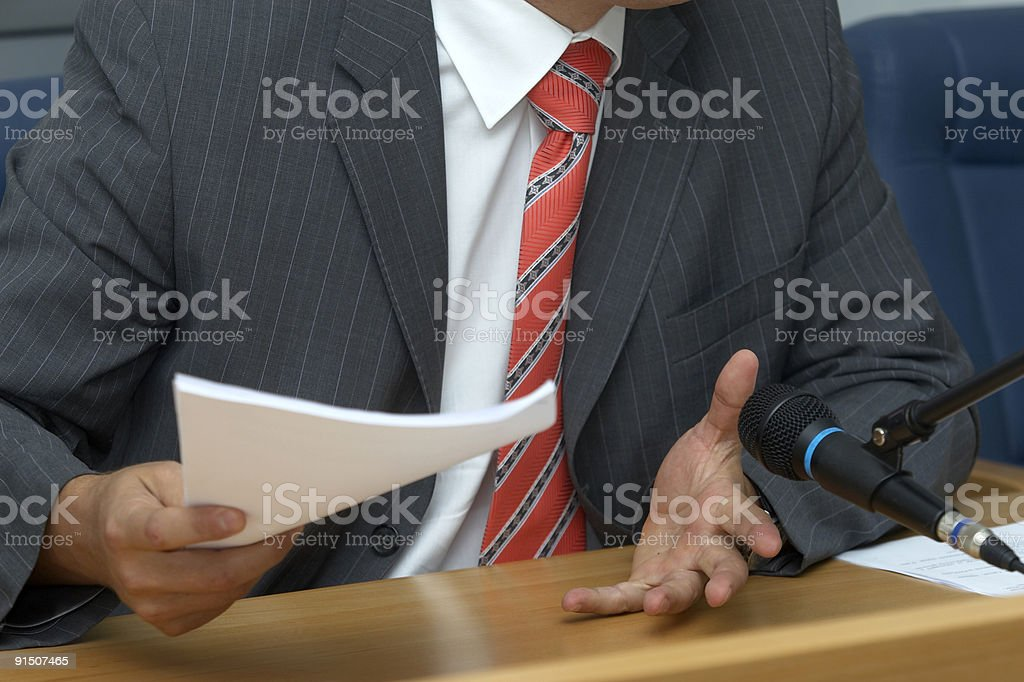 Man in a business suit holding documents at a conference royalty-free stock photo
