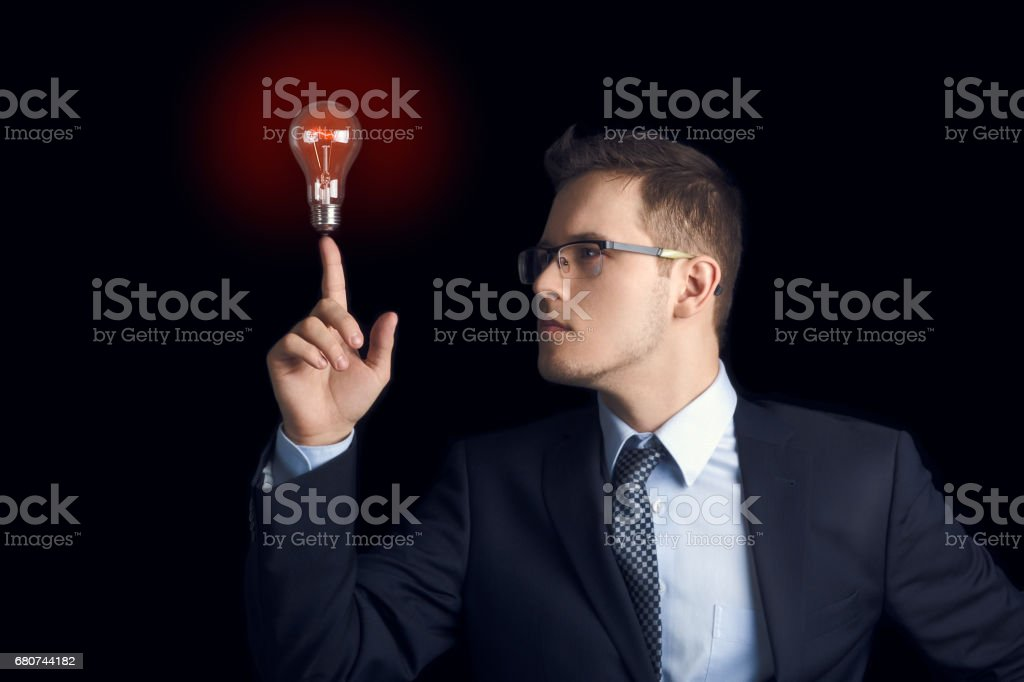 Man in a business suit looks at a burning light bulb located at his fingertip on a black background. stock photo