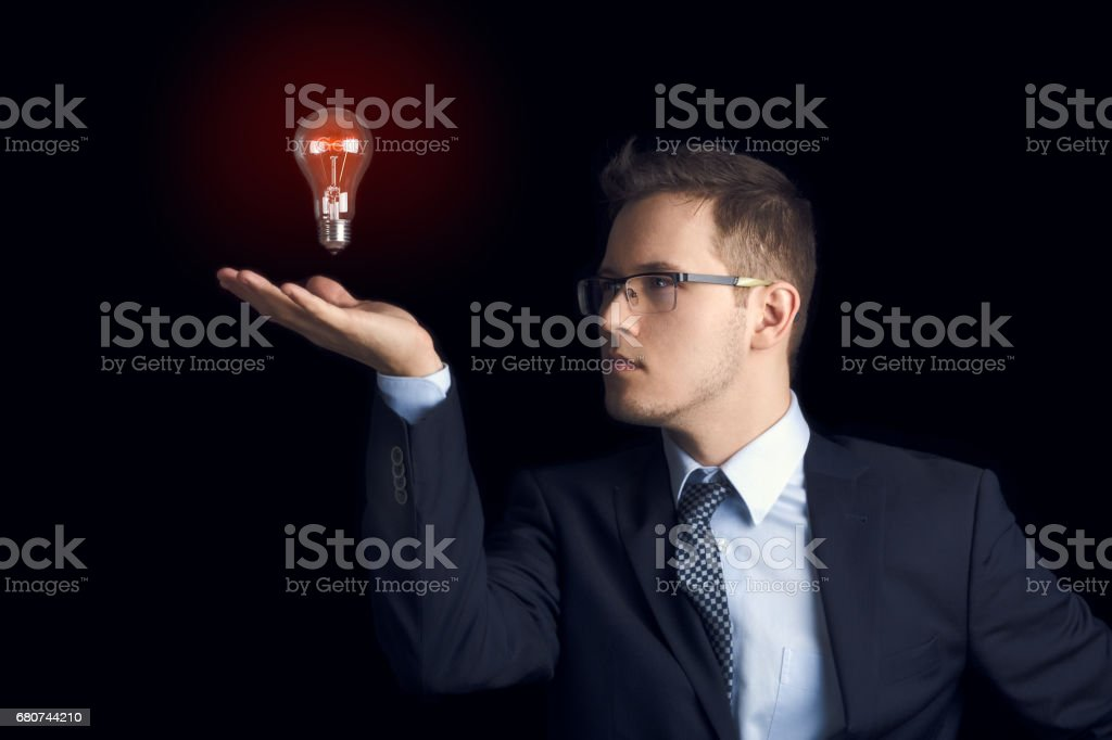 A man in a business suit looks at a light bulb above his palm as a symbol of knowledge and ideas, on a black background. stock photo