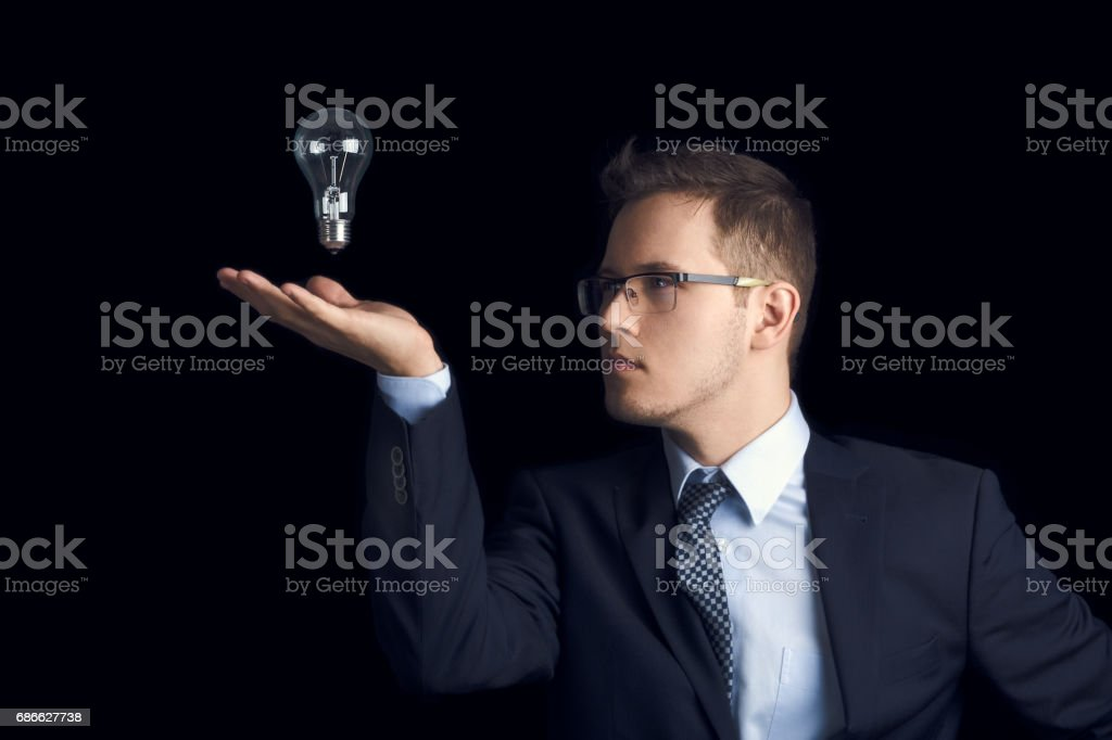 A man in a business suit looks at a light bulb over his palm against a black background. stock photo