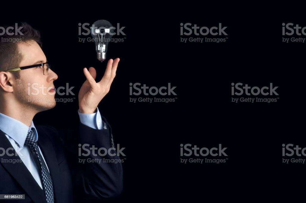 A man in a business suit looks at a lightbulb on a black background. stock photo